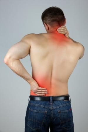 dolor muscular: Hombre joven con dolor de espalda y cuello en la zona roja Foto de archivo