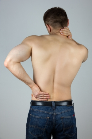 arthritis back: Young man with back and neck pain in the red zone