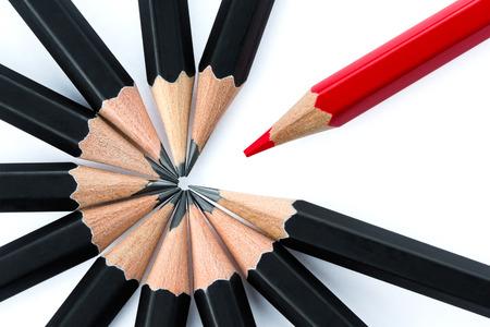 Een rood potlood staande uit de kring van zwarte potloden