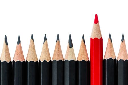 Ein Rotstift stehend aus der Reihe der schwarzen Bleistifte