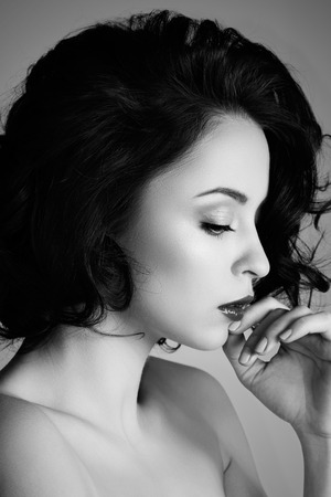 face side: Closeup side view of young beautiful thoughtful woman touching her lips. Black and white photo