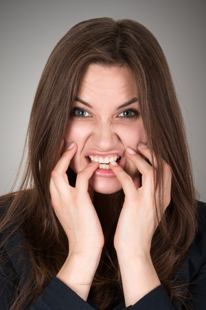 Frightened and stressed young business woman biting her fingers Stock Photo