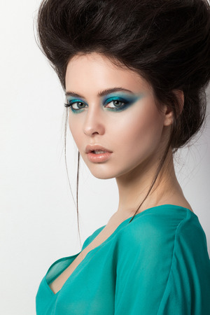 Seductive young brunette woman in a turquoise dress looking straight to camera photo