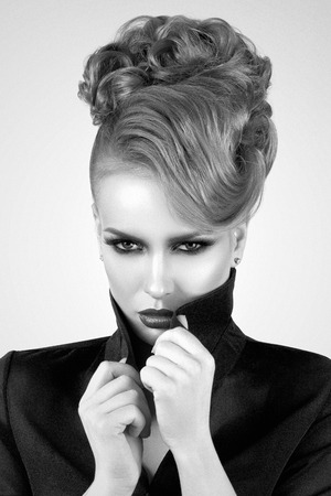 Portrait of beautiful lady with solid straight look sets her collar straight (in black and white) Фото со стока