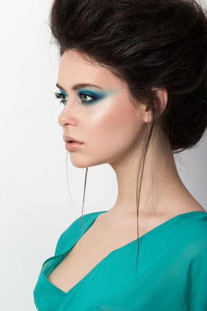 motton blue: Portrait of brunette girl in a turquoise dress looking into the distance Stock Photo