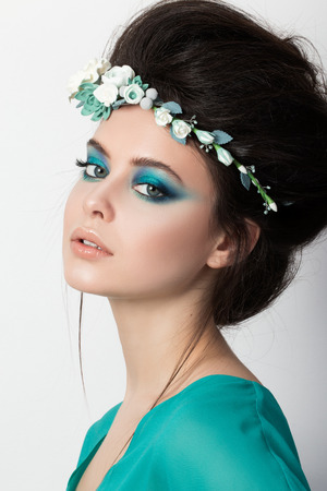 motton: Portrait of pretty brunette woman in turquoise dress and flowers diadem Stock Photo