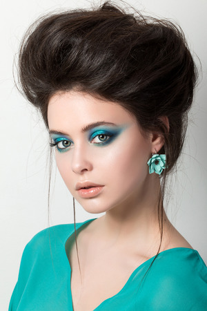 motton blue: Seductive young brunette woman in a turquoise dress wearing earing and looking straight to camera