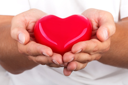 doctor holding gift: Male hands giving red heart