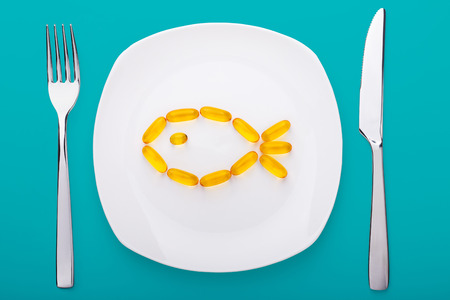 gels: fish oil soft gels lying on white porcelain plate in the form of fish (blue background)