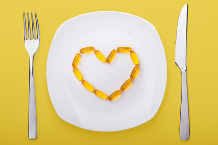 fish oil soft gels lying on white porcelain plate in the form of heart (yellow background) photo