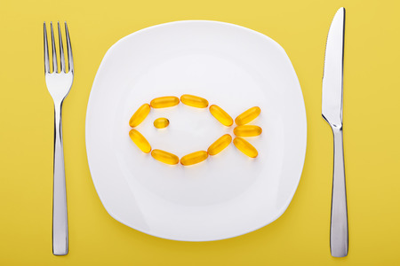fish oil: fish oil soft gels lying on white porcelain plate in the form of fish (yellow background) Stock Photo
