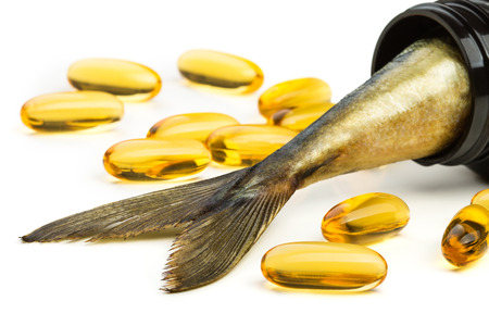 Fish oil capsules and fish tail in brown jar photo