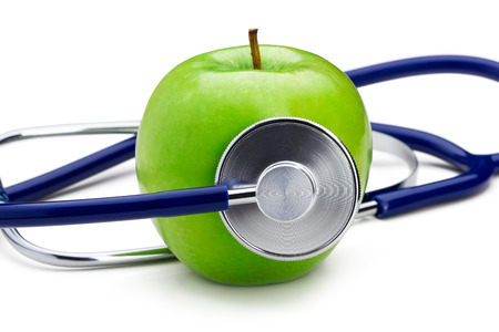 Stethoscope listening to green apple. Medical concept photo