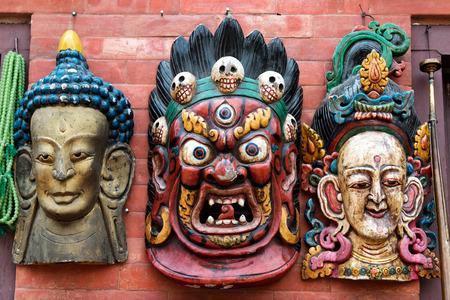 souvenir traditional: Three traditional Hindu masks hanging on red brick wall at Kathmandu souvenir market