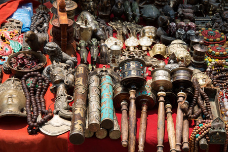 Bunch of tibetan traditional souvenirs lying on red table (market in Nepal, Kathmandu) photo