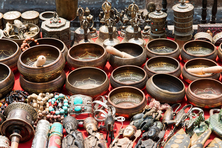 singing bowl: Bunch of tibetan traditional souvenirs lying on red table (market in Nepal, Kathmandu)