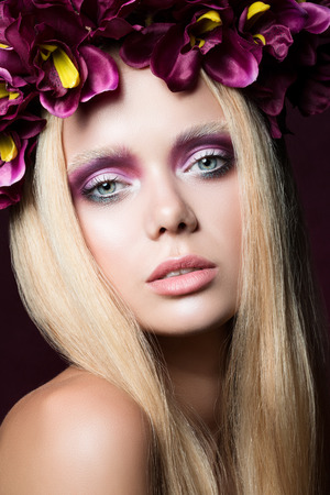 Beauty portrait of young blonde woman with purple floral wreath over dark background photo