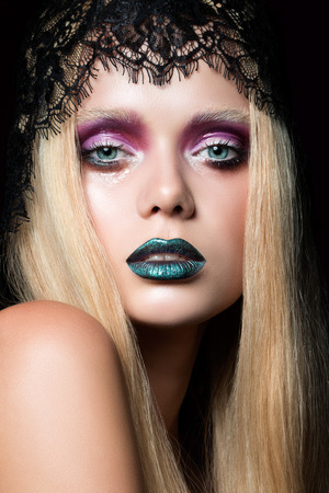 Fashion portrait of young woman with blue lips and wet eyelid effect stage make-up photo