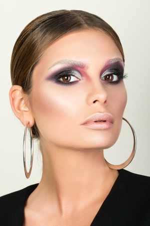 stage make up: Beauty portrait of adult woman wearing metal round earrings