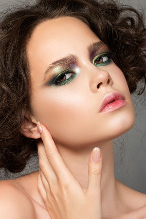 frizzy hair: Beauty portrait of young woman touching her face, catwalk beauty look