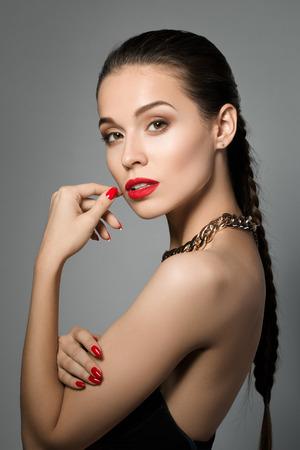 cabello rojo: Retrato de joven y bella mujer morena con maquillaje de la tarde sobre fondo gris