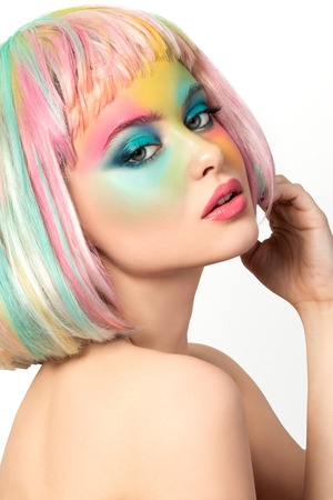 Portrait of young woman with funny rainbow coloured make-up touching her hair