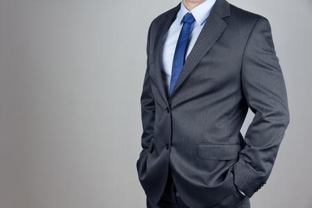 El hombre en traje de fondo gris
