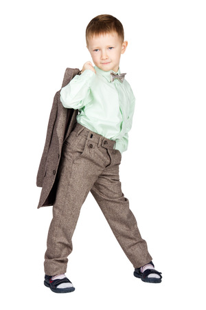 half turn: Young boy in grey suit and bow tie standing half turn, holding his jacket and looking on camera (isolated on white) Stock Photo