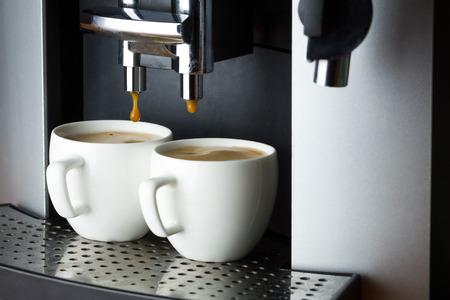 Twee witte kopjes espresso in koffiemachine Stockfoto