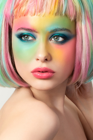 hand colored: Portrait of young woman with funny rainbow coloured make-up touching her hair