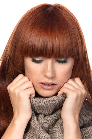 Young red-haired woman wrapping herself in warm knitted shawl photo