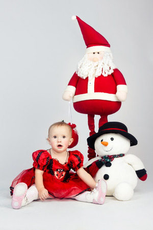 Little girl in red dress sitting on the floor near christmas toys and looking over camera with curiosity photo