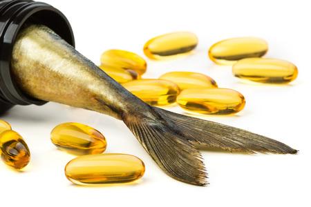 Fish oil capsules and fish tail in brown jar