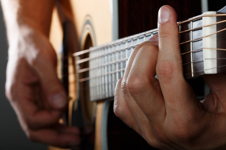 fretboard: Acoustic guitar player performing song