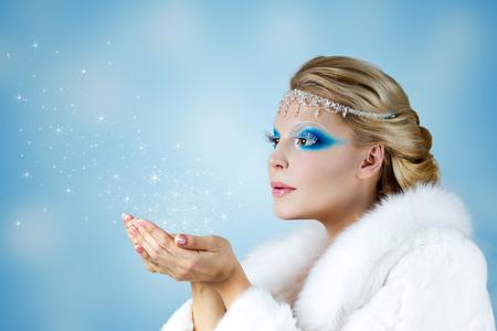 Winter Christmas Girl. Beautiful Woman Blowing Snow photo