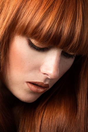 Red haired woman with freckles looking down (sensual look) photo