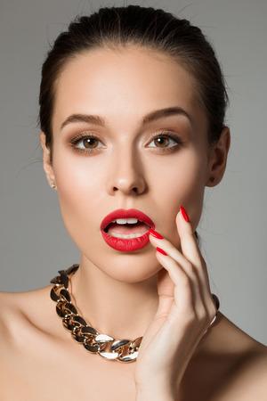 Schoonheid portret van verrast jonge brunette vrouw aan te raken haar gezicht