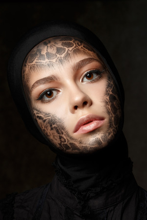 faceart: Portrait of young beautiful nun with faceart over dark background
