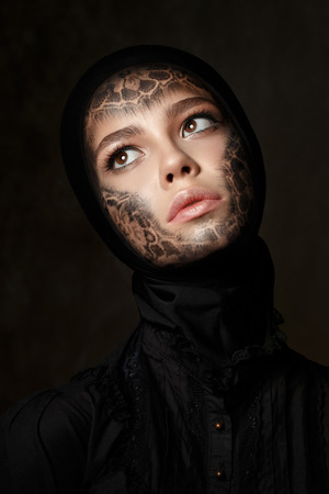 faceart: Portrait of young beautiful woman with faceart over dark background