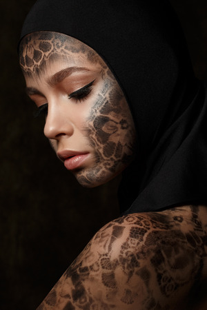 Portrait of young beautiful woman with bodyart over dark background photo