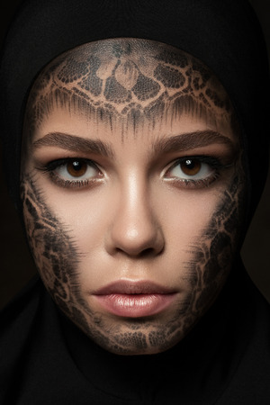 faceart: Close-up portrait of young beautiful nun with faceart over dark background