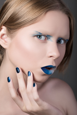 Close-up portrait of young amazed girl with fancy make-up touching her face photo