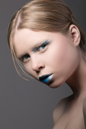 Close-up portrait of young surprised girl with unusual blue make-up photo