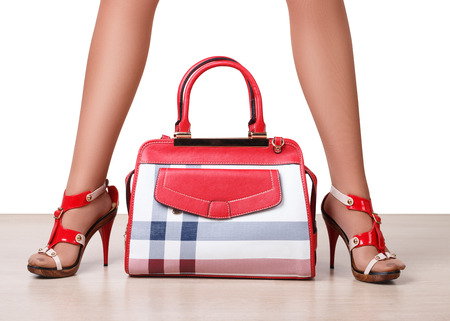 vanity bag: Female bag between beautiful womans legs in sandals Stock Photo