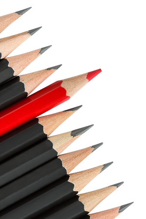 Een rood potlood staande uit de rij van zwarte potloden Stockfoto
