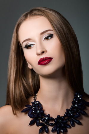 long neck: Beauty portrait of young brown-haired woman wearing necklace