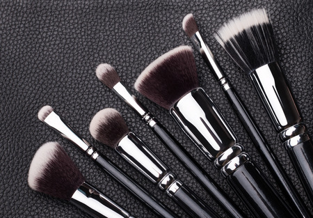 Set of professional makeup brushes over black leather background Stock Photo