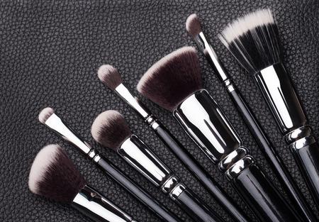 Set van professionele make-up borstels op de achtergrond zwart leer Stockfoto
