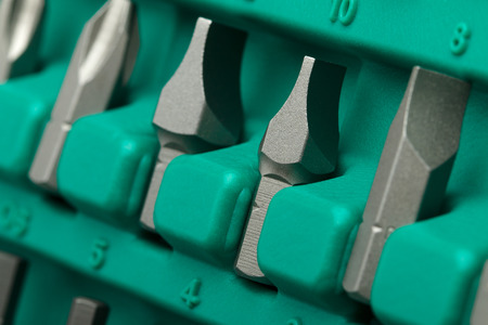replaceable: Set of tools closeup (straight and cruciform screwdriver tips in green plastic case)