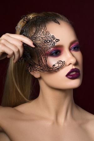 modelos negras: Close-up retrato de la belleza de la mujer bastante joven rubia con la noche de maquillaje la celebraci�n de la m�scara del partido negro en la mano.